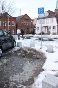 Ein Behindertenparkplatz in Travemünde an der Vorderreihe, auf dem ein Schneehaufen liegt