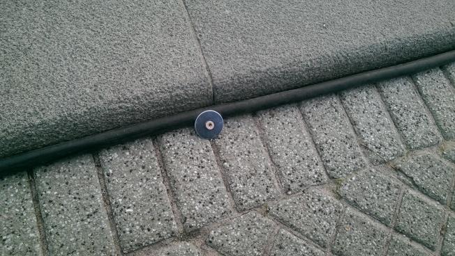 Kabel an abgesenkten Bordstein mit Schrauben und Unterlegscheiben fixiert